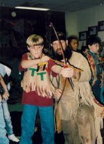 Mike helps a student get the feel of a hand-made bow.